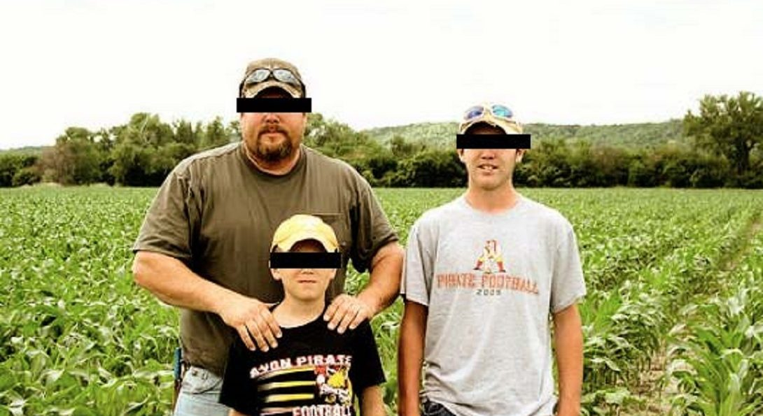 A farmer and his two sons stand in a crop field. Their eyes have been redacted.